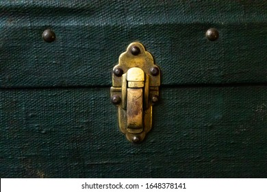 Old antique golden metal lock on green textile suitcase, close-up. Vintage retro styled textured toned photo