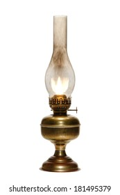 Old antique kerosene oil lantern brass hurricane lamp with hot burning flame casting light in a vintage glass chimney over fuel container metal base isolated on white