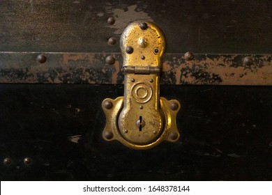 Old antique metal suitcase lock, close-up. Vintage retro styled textured toned photo