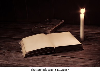 old antique opened book with burning candle near on the wooden table. Blank page