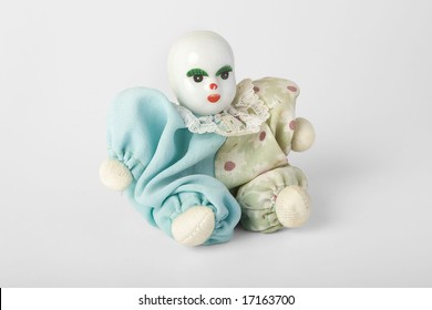 Old Antique Porcelain doll with dress sitting on the ground, isolated on white. clipping path included.