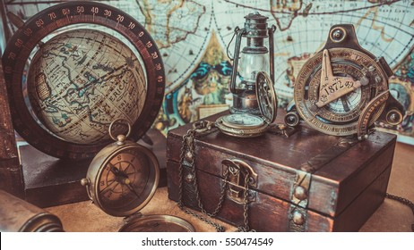 Old antique rare items collections including with a compass, oil lamp, globe model rotation on a wooden base and treasure chest of pirate and sailing on the ocean. (vintage style)