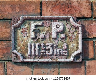 an old antique rusting british fire point sign on a brick wall used to indicate the distance to an available water supply