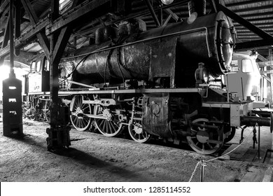 An old and antique steam locomotive in a hangar