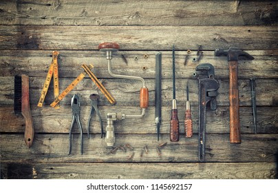 Old antique tools viewed from above on rough wood surface