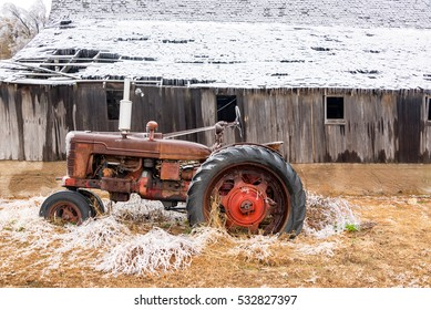 Old antique tractor covered in ice with a snow covered barn near Burrton, Kansas