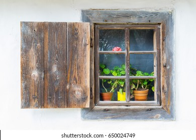 An old antique window with flowers in a vintage peasant white house in Ukraine. An antique wooden window frame with a door. National Museum Pirogovo in the outdoors near Kiev.