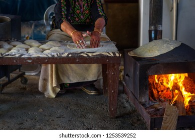 Old arab woman cooking traditional bedouin cuisine food - taboon bread or flatbread. Close up of Arab woman hands baking fresh dough for Taboon bread or  Laffa. Middle Eastern and Israel flat bread.