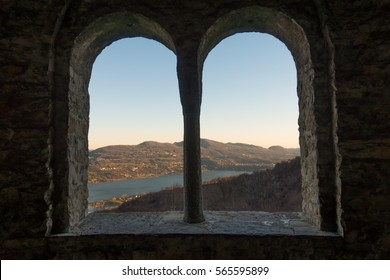 Old arched castle windows with a view on lake and mountains