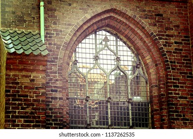Old arched church window  encased in a red brick wall, with copper decorations and reflections