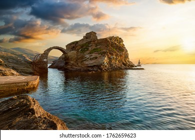 The old arched stone bridge leading to the ancient Castle of Andros island at the Cyclades of Greece during a beautiful summer sunrise