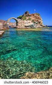 Old arched stone bridge and Lighthouse Tourlitis, in the beautiful town of Chora in Andros island, Cyclades, Greece