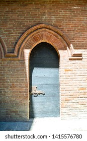 an old arched wooden door, closed by a deadbolt, outside a brick buildn.