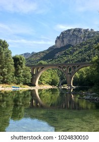 Old architecture Roman Aqueduct stone bridge over river in middle of France Ardeche Gorges du Tarn UNESCO world heritage area on sunny day with greenery mountain background