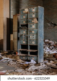 Old archival cupboard in an empty, run down office building. Scattered files and papers on the floor
