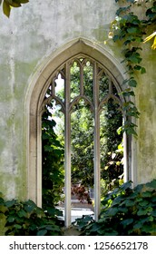 An old archway is covered in vines. It was once a window in a wall, but the glass has been removed. The wall is bare. A garden can be seen through the arch.