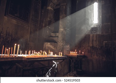 Old Armenian christian church interior with sun rays from the window falling on the candles. Religion, old architecture, christianity, travel, belief concept.