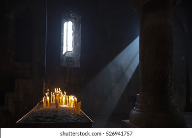 Old Armenian christian church interior with sun rays from the window falling on the candles.