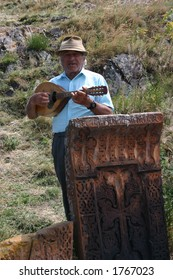 Old Armenian playing domra, Khachkars (Armeninan cross stones) on foreground
