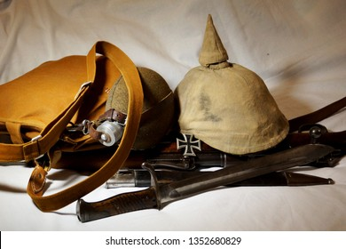 Old army gear from the German military of World War I. A duffel bag with canteen and traditional spiked helmet rest upon a bolt-action Mauser rifle and bayonet, along with Iron Cross award for valor.