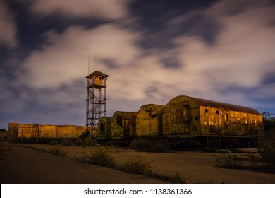 Old army watchtower in abandoned military base at night.