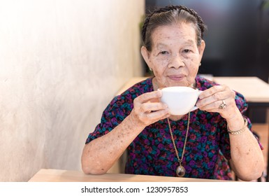 old asian female holding hot coffee cup, she relax in cafe,  retirement activity