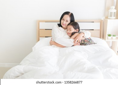 old asian female hug asian children on white bed, old asian woman and her daughter feeling happy in family time, retirement happiness, elderly activity, mother day