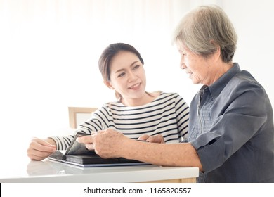 old asian female and young asian female looking photo book, they talk about old story, family time, mother day