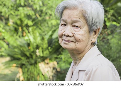 an old asian healthy woman is smiling