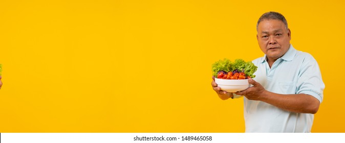 Old Asian man holding bowl of vegetables on diet, Healthy food and Thai senior people lifestyle concept on yellow banner background