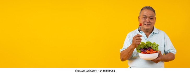 Old Asian man holding spoon with tomato and bowl of vegetables on diet, Healthy food and Thai senior people lifestyle concept on yellow banner background