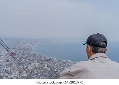 Old asian man is looking on the city of Hakodate, Japan. He is on top of the mountain, he is wearing blue hat and grey jacket. He took cable car to the view point.