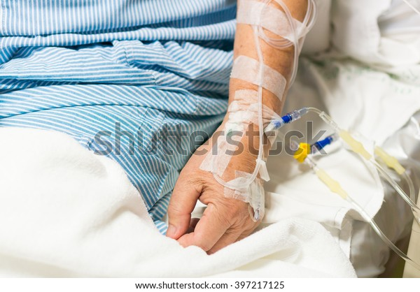 Old Asian man patient is on drip receiving a saline solution.Selective focus.