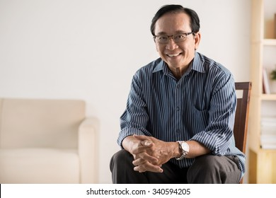 Old Asian man sitting on chair and smiling at camera