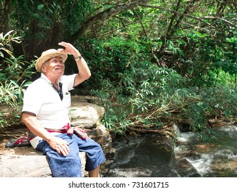 Old Asian man sitting on the water leg hanging. And looking forward to enjoying nature.