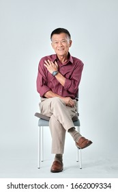 An old asian man wear red shirt and beige pants sitting on a grey chair and cross one's legs in studio white background. Isolated picture of happiness asian old man.