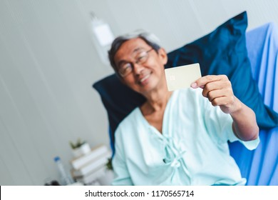 Old asian patient man showing credit card with happy and smile on patient bed