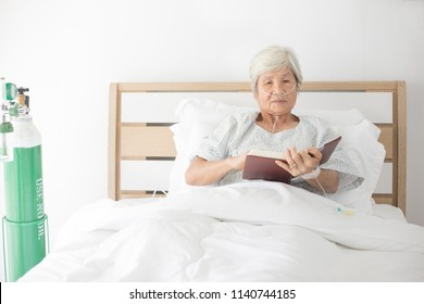 old asian patient reading a book on bed, old patient relax after admit in hospital