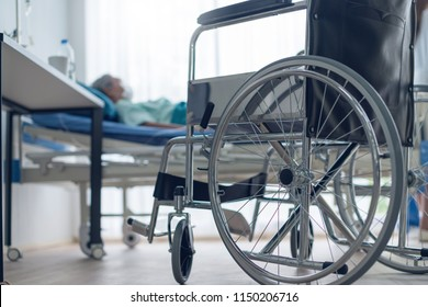 old asian senior disable laydown on bed with foreground of wheelchair in hospital