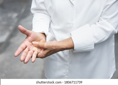 old asian senior woman suffering from trigger finger, cps or carpal tunnel syndrome