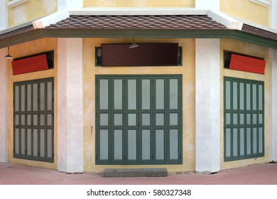 Old Asian style vintage wooden window / green door / yellow wall of colorful house