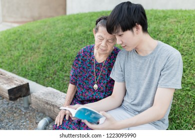 old asian woman and asian man reading a book in the garden, close up face of old asian woman, they feeling happy in family time