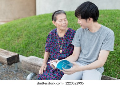 old asian woman and asian man reading a book in the garden, they feeling happy in family time