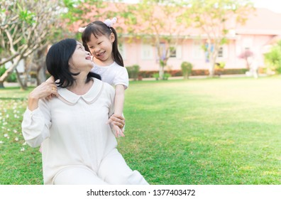 old asian woman relax with asian children on green nature background, they relax on green grass,  old asian woman hug and kiss asian girl, retirement happiness activity, child development, eye contact