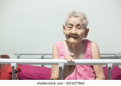 old asian woman sitting on patient bed, she feel happy and smile