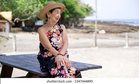 Old asian woman sitting on top of a table enjoying the tropical beach view.