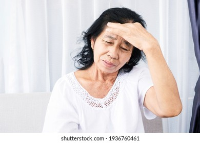 old Asian woman suffering from headache, migraine and feeling dizzy sitting at sofa hand holding her head