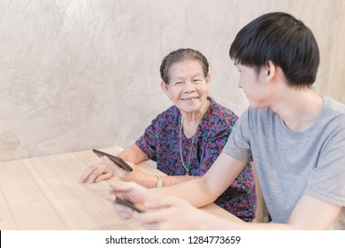 old asian woman talk with young asian man, they playing smartphone, they connect internet technology with smartphone, they feeling happy and smile