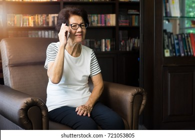 Old asian woman using smartphone for talking.