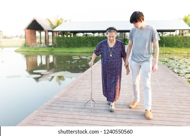 old asian woman and young asian man relax in garden, old asian woman use cane to walk on the bridge, walk training, they feeling happy, rehabilitation process,  mother's day
